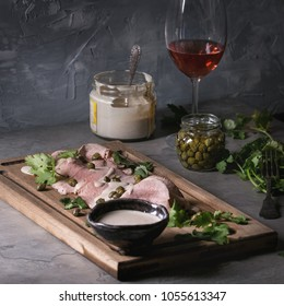 Vitello tonnato italian dish. Thin sliced veal with tuna sauce, capers and coriander served on wooden serving board, glass of rose wine and ingredients above over gray kitchen table. Square image