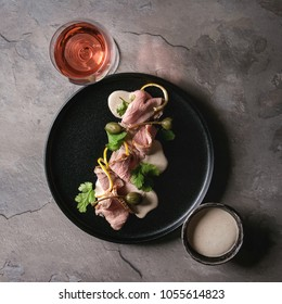 Vitello tonnato italian dish. Thin sliced veal with tuna sauce, capers and coriander served on black plate with glass of rose wine over gray texture kitchen table. Top view, copy space. Square image