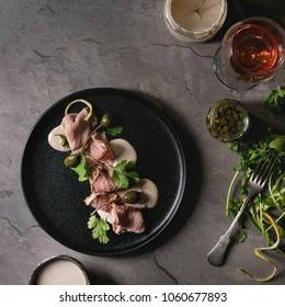 Vitello tonnato italian dish. Thin sliced veal with tuna sauce, capers and coriander served on black plate, glass of rose wine and ingredients above over gray texture kitchen table. Top view, space