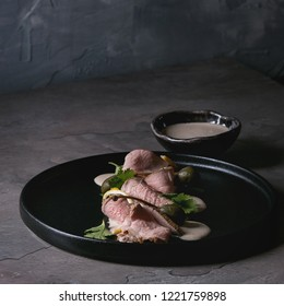 Vitello tonnato italian dish. Thin sliced veal with tuna sauce, capers and coriander served on black plate over dark texture background. Top view, space. Square image