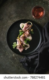 Vitello tonnato italian dish. Thin sliced veal with tuna sauce, capers and coriander served on black plate with glass of rose wine over old dark metal background. Top view, space