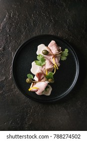 Vitello tonnato italian dish. Thin sliced veal with tuna sauce, capers and coriander served on black plate over dark texture background. Top view, copy space