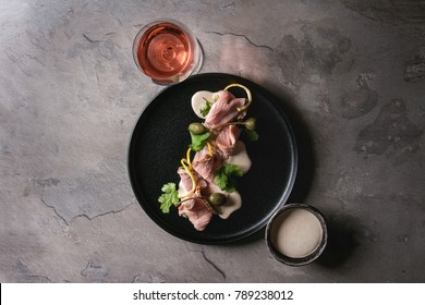 Vitello tonnato italian dish. Thin sliced veal with tuna sauce, capers and coriander served on black plate with glass of rose wine over gray texture kitchen table. Top view, copy space