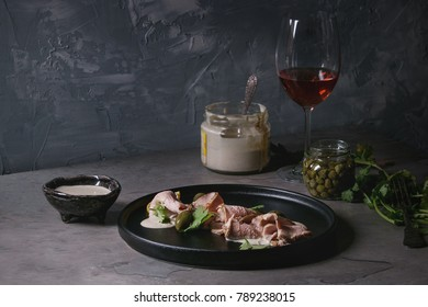 Vitello tonnato italian dish. Thin sliced veal with tuna sauce, capers and coriander served on black plate, glass of rose wine and ingredients above over gray texture kitchen table.