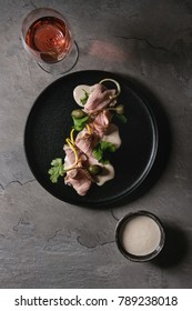 Vitello tonnato italian dish. Thin sliced veal with tuna sauce, capers and coriander served on black plate with glass of rose wine over gray texture kitchen table. Top view, space