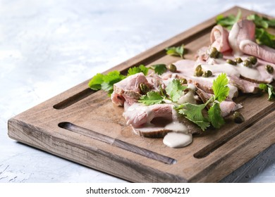 Vitello tonnato italian dish. Thin sliced veal with tuna sauce, capers and coriander served on wooden serving board over gray texture background.