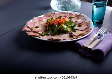 vitello tonnato on a serving plate with water