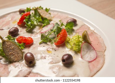 Vitello tonnato. Veal. Leaves of lettuce. Radish. Olives. Sauce. n a white square plate. On a wooden table is brown.