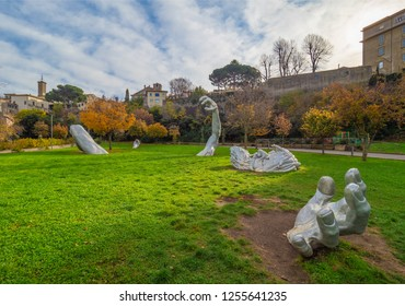 """Viterbo, Italy - 2 December 2018 - A sunday morning in the medieval city of the Lazio region with the modern sculpure of giant coming out of the earth, in the public garden, named """"Risveglio"""""""