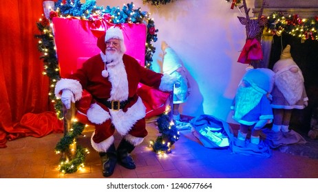 VITERBO, ITALY - NOVEMBER 25, 2018: Portrait of happy Santa Claus sitting on his throne decorated with christmas lights