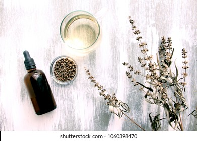 vitex agnus-castus dried flower and alcoholic tincture and herb tea on white wooden background