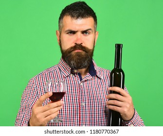 Viticulture and autumn concept. Man with beard holds glass of red wine isolated on green background. Sommelier tastes expensive beverage. Winemaker with strict face holds wineglass and bottle of wine.