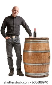 Viticulture concept with a man standing with his hand on an oak cask or barrel with a bottle of red wine on top isolated over white