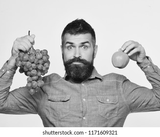 Viticulture and gardening concept. Man with beard holds bunch of green grapes and apple isolated on white background. Winegrower with surprised face holds grapes and red fruit. Farmer shows harvest.
