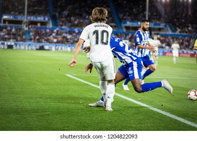 VITORIA, SPAIN - OCTOBER 06, 2018: Luka Modric (L) competes for the ball with Wakaso Mubarak (R) during the match between Deportivo Alaves and Real Madrid