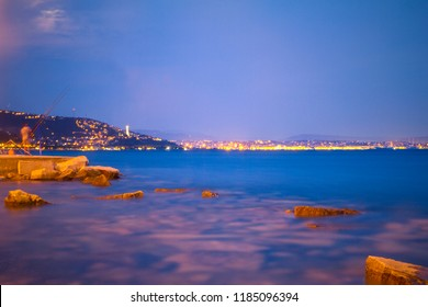 Vittoria Light and Trieste by night. Night photo, panorama of the city, city lights, Adriatic Sea landscape and coastline with rocks and night lights. Italy coast. Anglers on the coast. Night fishing