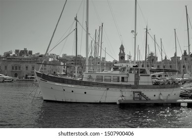 Vittoriosa, Malta, August 2019. Single mast schooner parked in the bay.