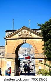 VITTORIOSA, MALTA - MARCH 31, 2017 - Tourists walking through an arch leading to the Grand Harbour marina, Vittoriosa (Birgu), Malta, Europe, March 31, 2017.