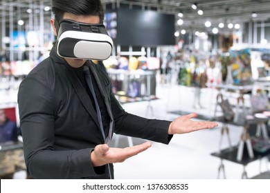 Vitual reality marketing technology for access entire product inventory in-store concept. Man suit use VR wearable device application for simulate color of suit in retail store.
