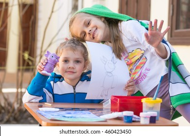 Vityazevo, Russia - April 24, 2016: Two girls painted Luntik at a table in the garden