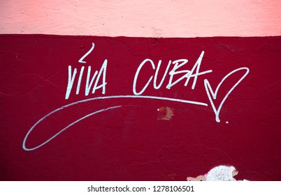 Viva Cuba inscription on a red and pink wall meaning live cuba for the young people, sun and beaches
