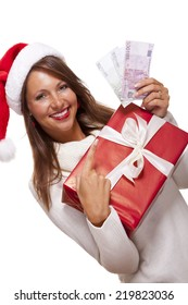Vivacious beautiful young woman wearing a Santa hat with a large red Christmas gift and money, conceptual of successful Xmas shopping and payment, on white
