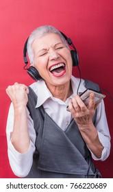 Vivacious, classy senior elderly lady listening to her favorite music through big headphones