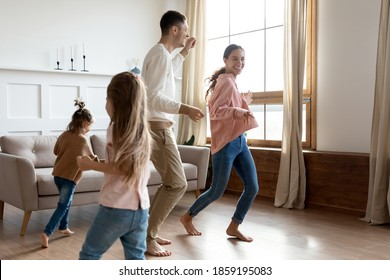 Vivacious family with 2 little daughters play together in cozy living room, people listen funky music dance run barefoot on warm floor at modern own apartment. Happy homeowners enjoy playtime concept