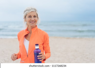 Vivacious fit woman walking on a beach in colorful sportswear carrying a blue bottle of water smiling at the camera