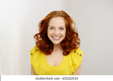 Vivacious friendly attractive young redhead woman looking at the camera with a motivated expression and beaming smile over a light colored wall