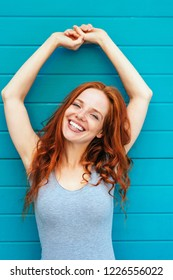 Vivacious fun young redhead woman laughing and holding her arms stretched above her head against a blue wall