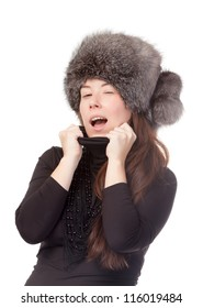 Vivacious woman in a winter outfit with a fur hat on white background