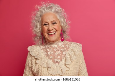 Vivacious wrinkled woman with curly hair smiles positively glad receive congratulations from children celebrates anniversary enjoys life wears jumper with lace, isolated on pink. People, age, emotions