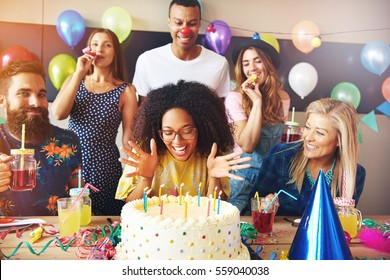 Vivacious young African woman celebrating her birthday getting ready to blow out the candles on the cake watched by a smiling group of friends