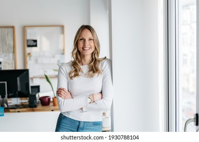Vivacious young business woman with a lovely warm friendly smile relaxing leaning against an interior pillar at the office with folded arms grinning at the camera