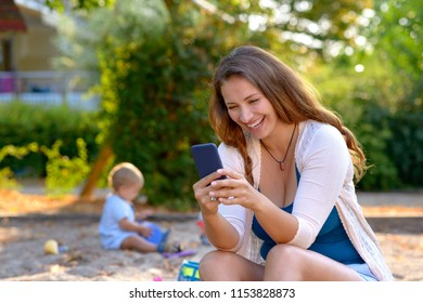 Vivacious young mother laughing at a text message on her mobile phone as she sits outdoors in a playground watching her baby son playing with his toys