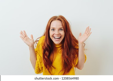 Vivacious young redhead woman with a delighted expression gesturing with her hands and looking at the camera with a beaming smile