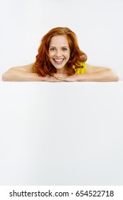Vivacious young redhead woman with a large blank white sign leaning on the top smiling happily at the camera