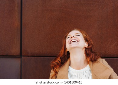 Vivacious young woman enjoying a good joke throwing back her head and laughing in front of a rust colored wall with copy space