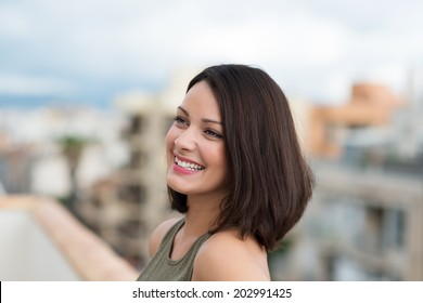 Vivacious young woman with shoulder length brunette hair and a beautiful smile smiling happily as she looks away to the left of the frame