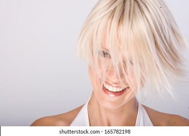 Vivacious young woman with a trendy blond hairstyle flicking her short hair in the air as she laughs at the camera