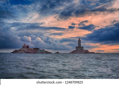 Vivekananda Rock memorial and the 133-feet tall stone statue of Thiruvalluvar at Kanyakumari, Tamil Nadu, India, in the Indian Ocean against the dark cloudy sky in the evening.