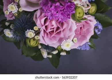 Vivid arrangement of rose flowers and hyacinth  against gray background. Studio photography of flowers in violet colors