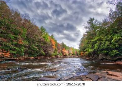 Vivid Autumn colors abound along the rapids of a wild river in the Appalachian mountains of Maryland