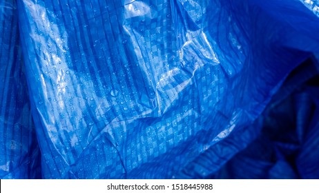 Vivid blue plastic Tarpaulin with water droplets on its surface.