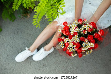 vivid bouquet of small red roses and carnations in girls hands sitting on a ground, diagonal composition