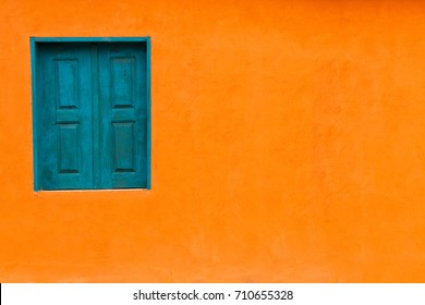 Vivid bright orange colour facade with blue-green window and large empty orange wall texture background space.