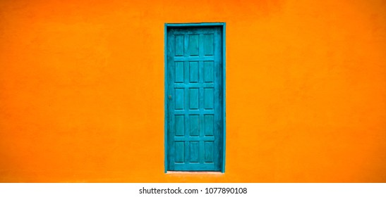 Vivid bright orange wall house facade with blue green closed door in the centre of large empty orange wide wall texture background space in panorama banner format.