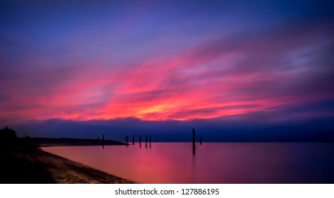 Vivid color lights up this magnificent landscape as the sunset brilliantly fills the blue sky with bright pink, yellow and purple and reflects in the smooth ocean water.