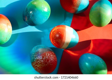 Vivid colored eggs for Easter standing on red and blue papers background